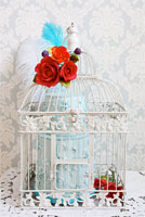 Antique birdcage with pale blue floral cake complimented with orange and red sugar roses.