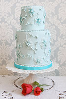 Blue cake embellished with blue sugar flowers.