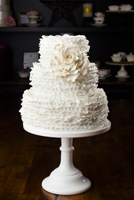 Three tier cake encased in layers of ruffles and accented with an antique white gumpaste rose. A tribute to Maggie A.
